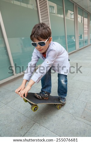 portrait of little boy with sunglasses on the skate, external - stock photo
