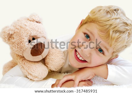Portrait of little boy with teddy bear on white background - stock photo