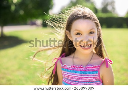 Portrait of little caucasian girl in the meadow in the park - stock photo