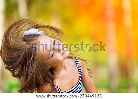 Portrait of Little caucasian girl  wind with flying hair, against green of summer park. - stock photo