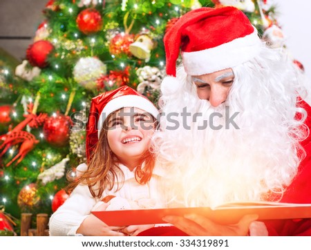 Portrait of little charming baby girl with Santa Claus reading magical Christmas story, enjoying wonderful festive fairy tale - stock photo