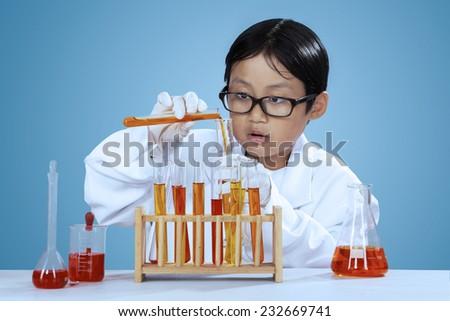 Portrait of little chemist mixes the chemical fluid, shot over blue background - stock photo