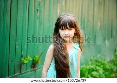 Portrait of little child girl with long brunette hair posing outdoors on a summer day - stock photo