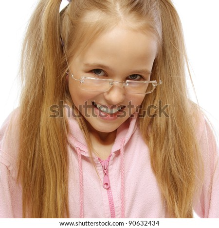 Portrait of little cunning smiling happy girl wearing pink jacket and eyeglasses, holding hands in pockets against white background.