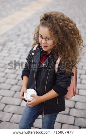 Portrait of little curly hipster girl in glasses with coffee. Urban style. Autumn. Outdoor. Copy-space