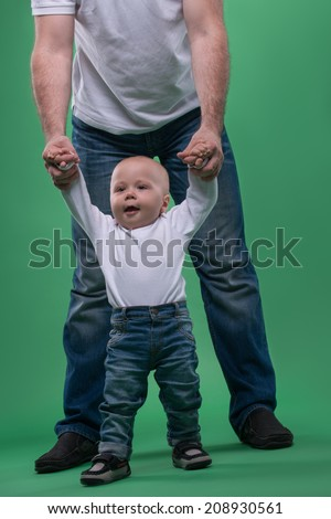 Portrait of little cute baby boy making first steps with his father, walking with support, isolated on green - stock photo