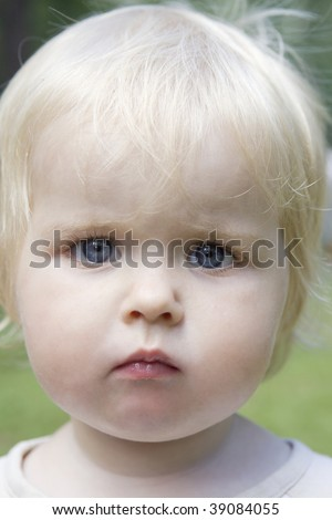 portrait of little cute blond serious baby girl
