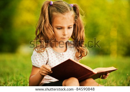 Portrait of little cute fair-haired girl reading book, sitting at summer green park. - stock photo