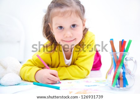 Portrait of little cute girl is drawing