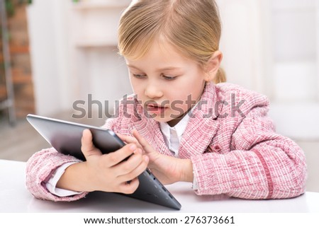Portrait of little cute girl wearing pink suit. Girl sitting at table and using tablet computer. Room interior as a background - stock photo