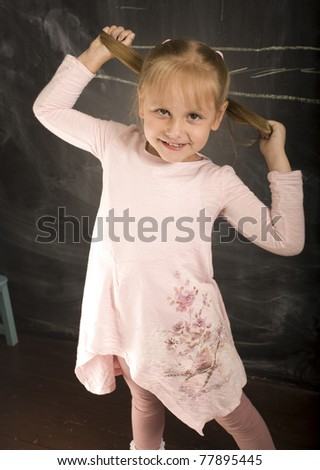 portrait of little cute girl with chalk writing on blackboard - stock photo