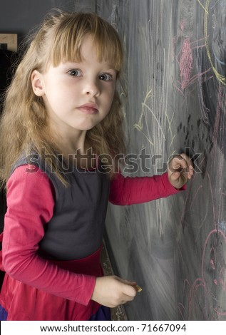 portrait of little cute girl writing on the blackboard