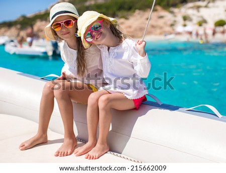 Portrait of little cute girls enjoying sailing on boat in the open sea - stock photo