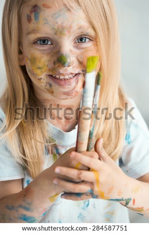 Portrait of Little dirty with paints smiling  girl with brush  - stock photo