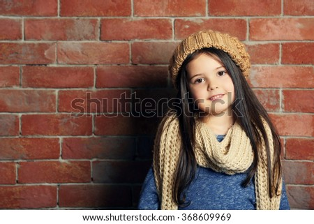 Portrait of little fashion kid girl in knitted cap and scarf on bricks wall background - stock photo