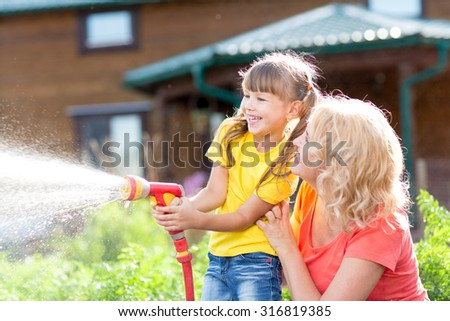 Portrait of little gardener girl with mother watering on lawn near house - stock photo