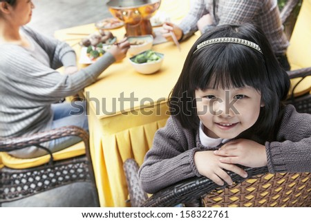 Portrait of little girl at family meal - stock photo