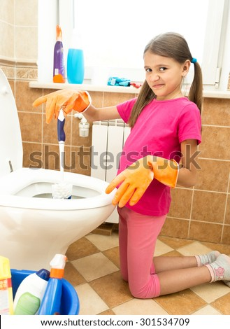 Portrait of little girl cleaning toilet with disgust
