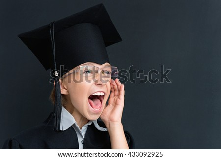 Portrait of little girl crying at the black chalkboard in classroom - stock photo