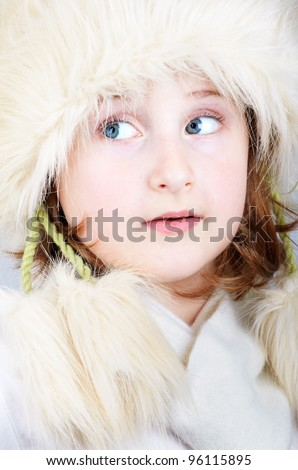 Portrait of little girl dressed very elegant with furry hat.