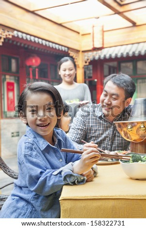 Portrait of little girl eating dinner with her family - stock photo