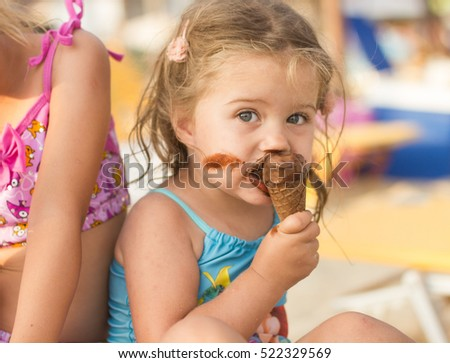 Portrait of little girl eating ice cream on the beach.