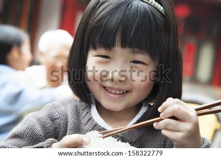 Portrait of little girl eating rice - stock photo