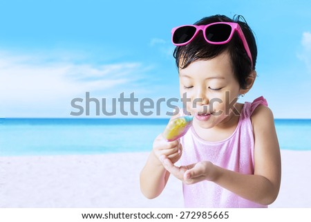 Portrait of little girl enjoy a melt ice cream on the beach while wearing swimwear - stock photo