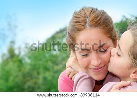 Portrait of little girl giving kiss to her mom - stock photo