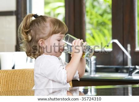 Portrait of little girl having drink in domestic environment - stock photo