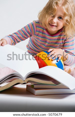 Portrait of little girl  holding a ball, a sketch-book and looking at the camera - stock photo