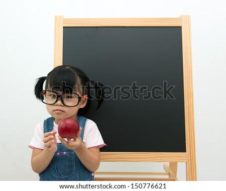 Portrait of little girl holding apple posing in front of the blackboard - stock photo
