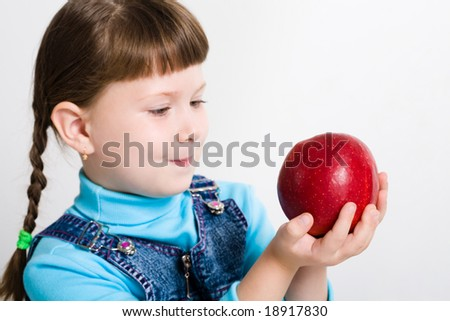 Portrait of little girl holding big red apple in hands and watching at it - stock photo
