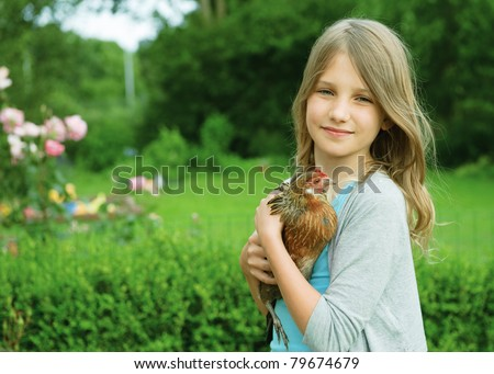 Portrait of little girl holding chicken in hands