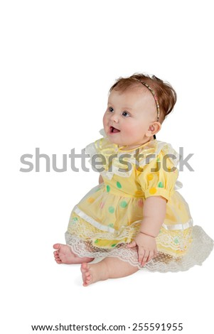 Portrait of little girl in a yellow dress sitting and looking sideways isolated on a white background - stock photo