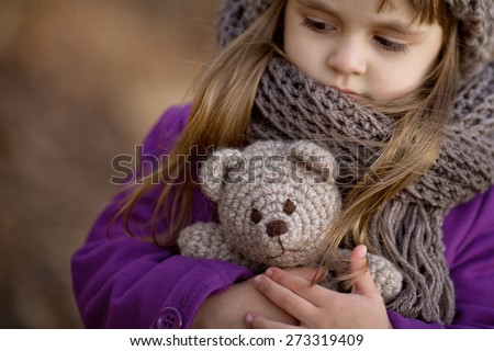 portrait of little girl in brown hat and scarf and purple coat holding teddy bear in her hands in the park
