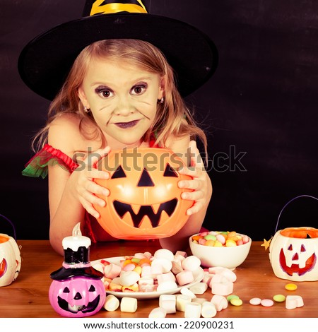 Portrait of little girl in costume witch on Halloween party