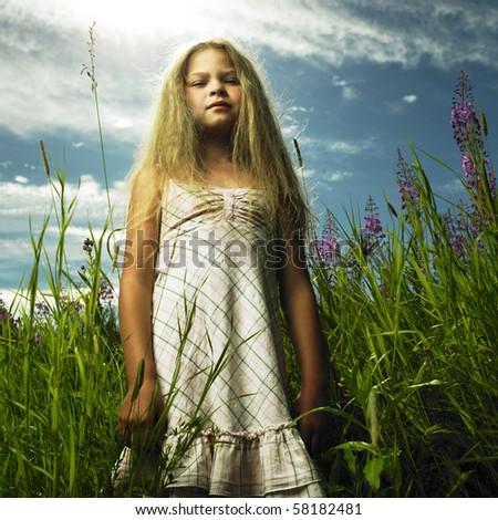 Portrait of little girl in flower meadow - stock photo
