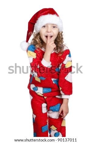 Portrait of Little girl in pajamas and santa hat with silence gesture over white background - stock photo