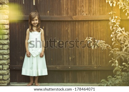 Portrait of little girl in white dress wooden fence - stock photo