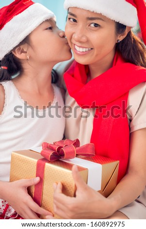 Portrait of little girl kissing her mother while giving thanks for Christmas present - stock photo