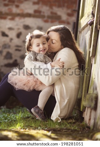 Portrait of little girl kissing her pregnant mother - stock photo