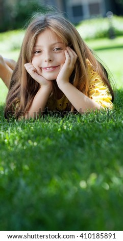 portrait of little girl laying on the grass in summer environment