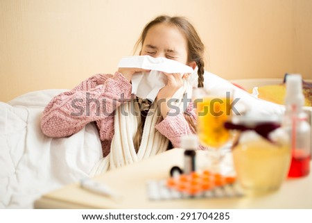 Portrait of little girl lying in bed and blowing nose in paper handkerchief - stock photo