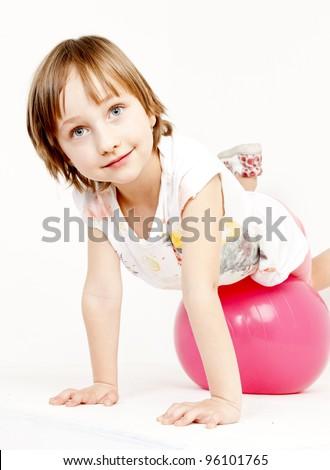 portrait of little girl lying on a ball - stock photo