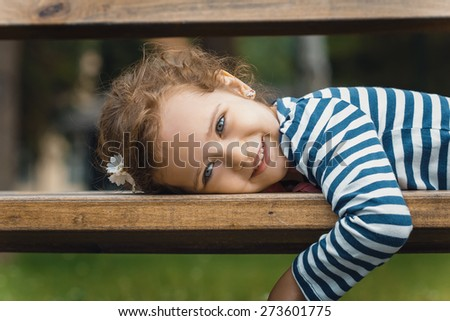 Portrait of little girl lying on bench in a park, leisure in the nature. Close-up - stock photo