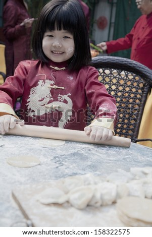 Portrait of little girl making dumplings in traditional clothing - stock photo