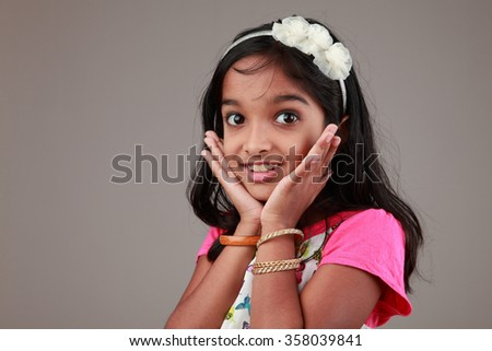 Portrait of little girl of Indian origin with a excited face - stock photo