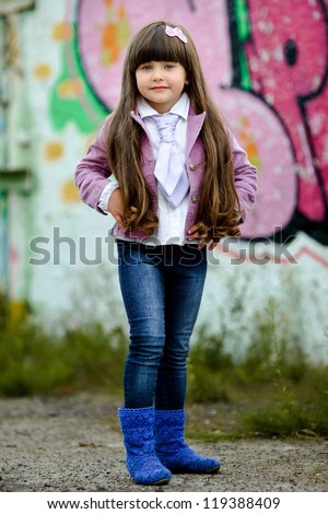 portrait of little girl outdoors in a pink jacket - stock photo