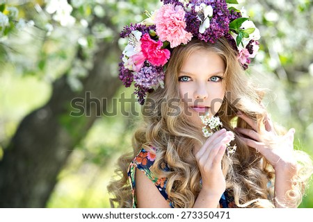 Portrait of little girl outdoors in spring with flower wreath - stock photo